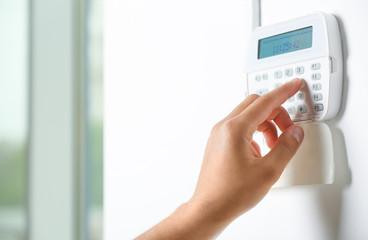 Obraz Male hand pressing the code on a house alarm - fototapety do salonu
