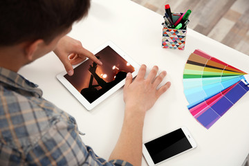 Man working with color palette and tablet at office