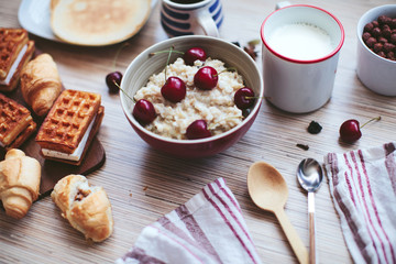 rich breakfast of porridge with cherries and pastry