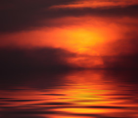Fiery sunset with reflection in water