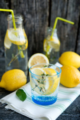 Cold refreshing lemonade with lemons and a thyme