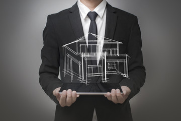 Businessman showing a model of the house