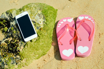 Flipflops and mobile phone on sandy ocean beach vacation concept, top view flat lay style