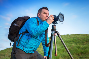 Landscape photographer with tripod over blue sky