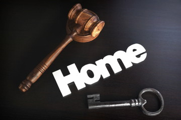 Judges Hammer or Gavel With Home Sign On Dark Background