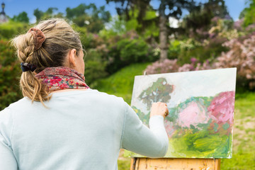 Back view of a female artist working outdoors in the park or gar