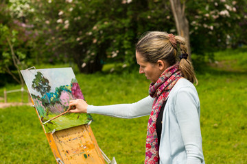 Female painter painting outdoors