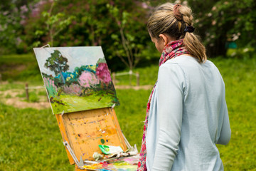 Female artist painting outdoors
