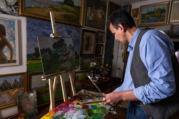 Middle-aged male artist mixing colors in a gallery