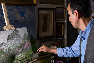 Contemplative male painter ending his masterpiece