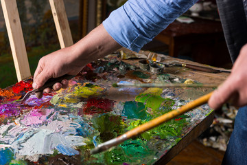 Male artist's hand working with palette