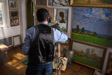 Male painter working on an easel in a studio