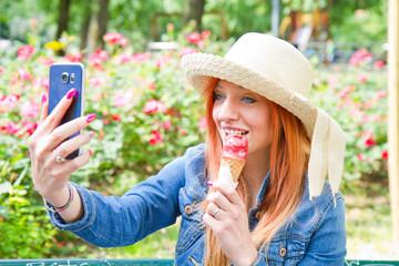 giovane ragazza al parco che si fa un selfie mentre mangia un gelato
