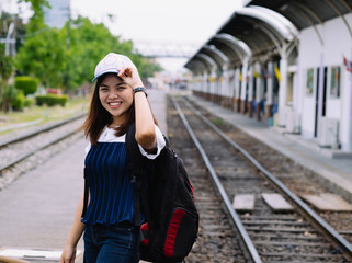 young asian girl waiting for the train in station,waiting train with smile and happy moment, single alone woman at train station with back pack for travel, filter effect