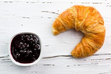 Croissant mit Marmelade auf weißem Holzbrett, Sicht von oben, N
