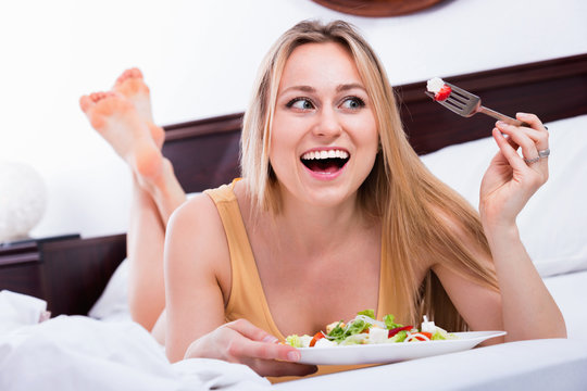 Blond woman in underwear sitting in the bed and enjoying a salad