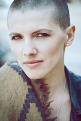 Closeup portrait of sad beautiful Caucasian white young bald girl woman with shaved hair head in leather jacket and scarf shawl looking in camera, toned with Instagram filters in blue color