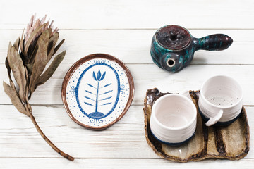 Close-up of clay tea set composition. Teapot, two cups on saucer, plate and rare flower served on white wooden table. Clay tea set for two in village style .