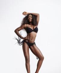 black woman in bikini is dancing