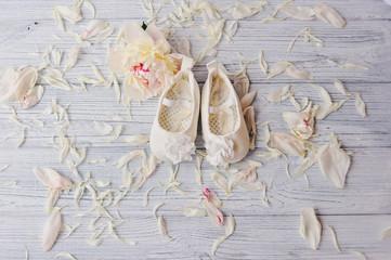 Милые беленькие туфельки  для маленькой девочки и нежный цветок