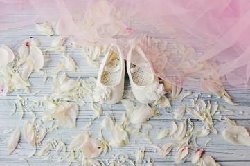 Милые беленькие туфельки  для маленькой девочки на рассыпанных лепестках белых цветов