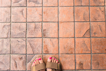 Feet selfie from upper view of a woman traveler in sandal during a tour trip around the world. Tourist take a photo of her own leg.