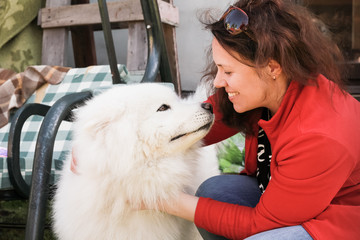 Happy young woman with white Samoyed dog