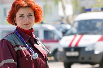 Happy female paramedic standing at ambulance machines background