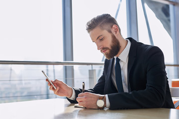 businessman writing notes from smartphone at modern office
