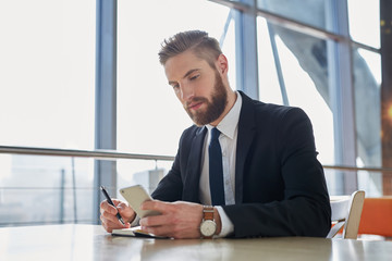 Handsome businessman writing notes from smartphone at modern off