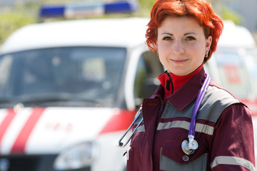 Positive female paramedic standing at ambulance machines background