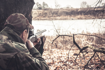 Door stickers Hunting Hunter man with gun aiming and prepared to make a shot during hunt