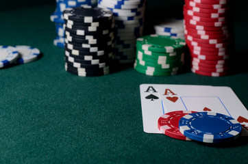 Casino chips and pair of aces on the green table. Poker game