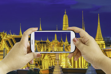 Smartphone photographing Wat Phra Kaew, Temple of the Emerald Buddha,Grand palace at twilight in Bangkok, Thailand
