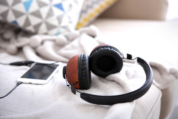 Stylish headphones and mobile phone on couch