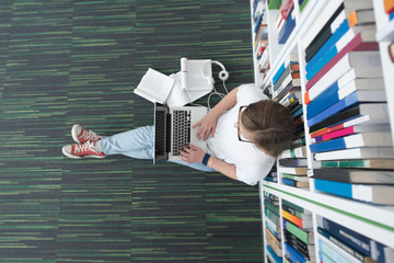 female student study in library, using tablet and searching for