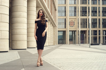 Young elegant girl posing at city street. Pretty beautiful business woman in elegant black dress against city background. Full length horizontal portrait.