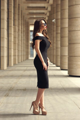 Young stylish classy elegant girl in sexy black dress and sunglasses with dark long curly hair standing at road between columns. Fashion style portrait