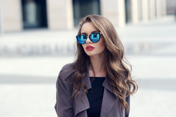Outdoor closeup fashion style portrait of young pretty stylish girl with long curly hair wearing sunglasses