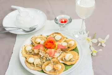 Baked scallops with butter and soy sauce in natural scallop shell delicious Thai seafood.