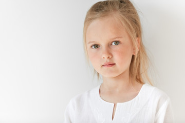 Six-years old girl with blond hair looking at you sideways with neutral emotions. Morning light and white clothes add simplicity and beauty to her attractive child appearance.