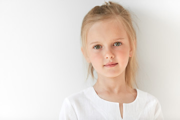 Pretty little girl with Caucasian traits looking peacefully and standing still like obedient child. She looks beautiful, attractive, nice, kind and well-mannered.