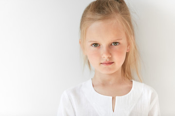 Close up portrait of little white-skinned girl looks straight forward and closely watching you. Blond baby stares at you showing her interest and curiosity as well as readiness to listen.