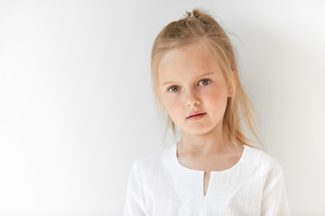 Little blond girl with attractive appearance posing in white background. Natural beauty and morning light suit her pretty and restful facial expression.