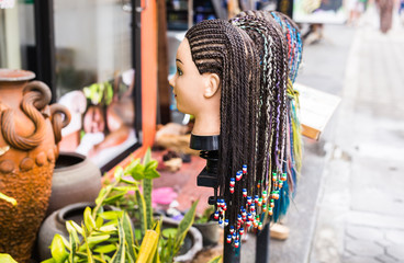 Female mannequin head with braided pigtails hairstyle decorated beads