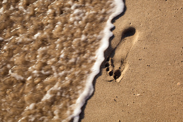 Traces of feet in the sand on the beach