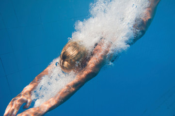 Blonde girl diving, underwater view