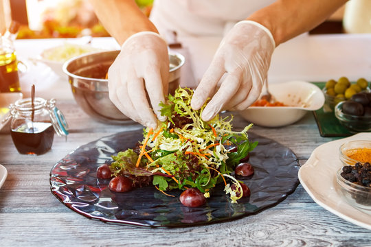 Hands touch salad on plate. Hands of cook in gloves. This dish is almost ready. Salad with grape and arugula.