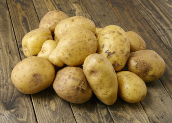 A pile of uncooked potatoes on a wooden counter top background