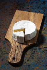 Camembert cheese on a cutting board, top view